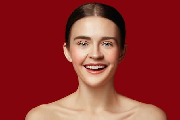빨간 스튜디오 벽에 젊은 여자의 완벽하고 깨끗한 피부