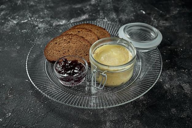 完璧な前菜-黒いテーブルの上にジャムとライ麦パンが入った瓶に入った鶏レバーのパテ。クローズアップ、セレクティブフォーカス