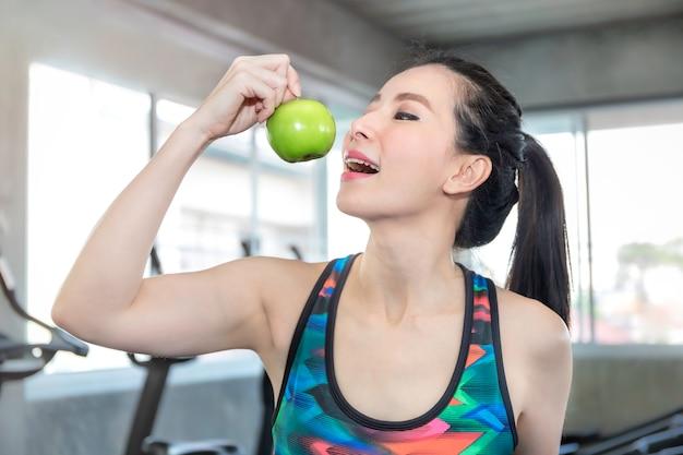 フィットネスジムでのトレーニングの前に食べるための青リンゴを保持しているスポーツウェアで完璧なアジアの女性。