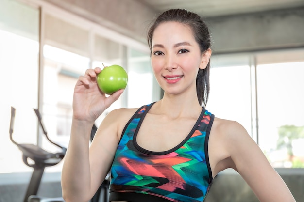 Perfect asian woman in sportswear holding green apple for eat before workout at fitness gym.