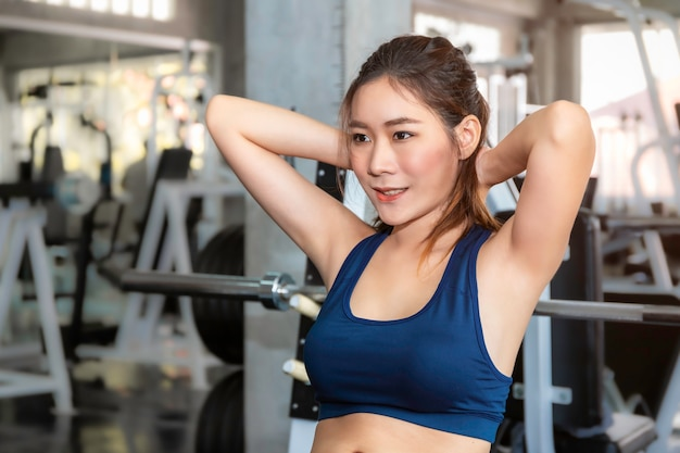 Perfect asian woman in sportswear training sit up at fitness gym.