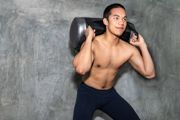 Perfect athletic asian man training with power bag at gym.