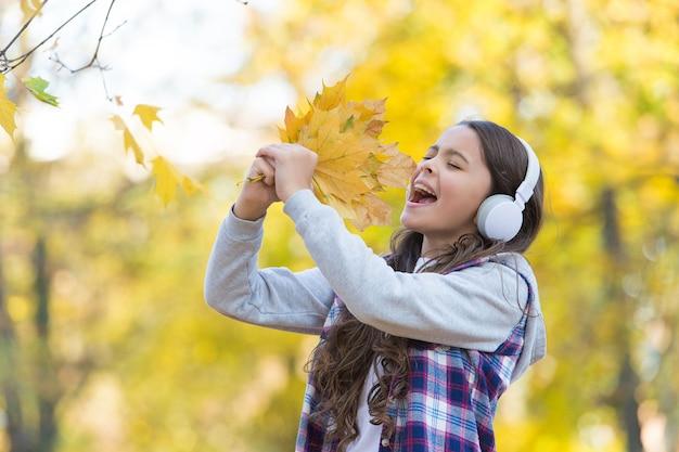 Идеальный осенний день веселой девушки слушать аудиокнигу или музыку в наушниках в осеннем парке