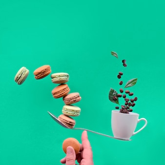 Perfect balance concept. balancing cup of coffee and macaronos on index finger. creative square food composition, copy-space on trendy biscay green paper background.