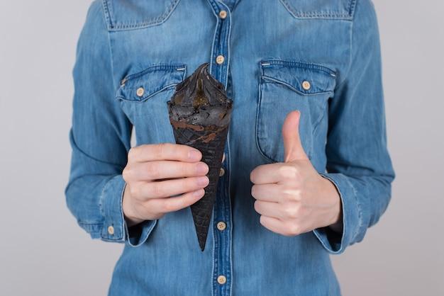 あなたのコンセプトに最適な最良の選択。手にアイスクリームを保持している指をあきらめるシンボルを作る幸せな嬉しい楽しい自信を持ってティーンエイジャーのトリミングされたクローズアップ写真孤立した灰色の背景