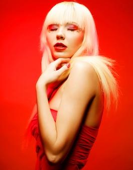 赤い背景の上の赤いドレスの完璧な金髪モデル。ファンタジーメイク。