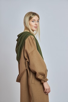 Perfect blonde woman with a scarf around her neck and head. clothing for cold autumn and winter weather