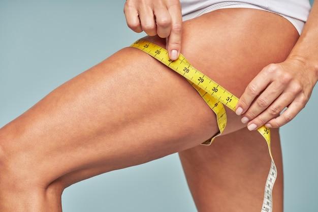 立っている間に巻尺で彼女の足を測定している女性の完璧なボディクロップドショット