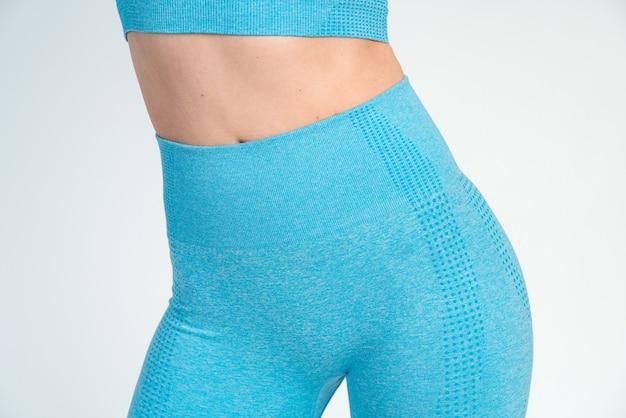 완벽한 몸. 흰 벽에 포즈를 취한 파란색 스포츠 옷을 입은 여성의 모습. 스포츠 및 레크리에이션 개념