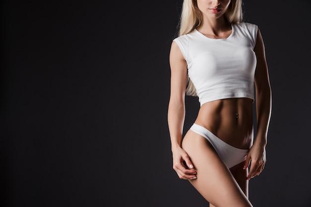 Идеальное тело молодой спортивной девушки на темном
