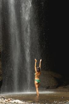 완벽한 몸. 강력한 폭포 근처에서 수영하면서 두 팔을 올리는 귀여운 여성의 실루엣