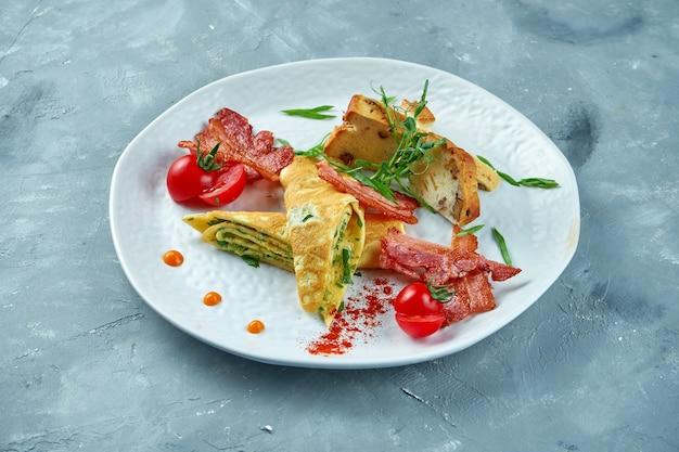 完璧な朝食-白い皿にほうれん草、ベーコン、焼きたてのパンとスクランブルエッグ。おいしいオムレツ
