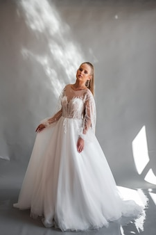 Perfect bride portrait of a girl in a long white dress beautiful hair and clean delicate skin