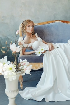 完璧な花嫁、長い白いドレスを着た女の子の肖像画。美しい髪と清潔で繊細な肌。結婚式の髪型金髪女性。手に白い花を持つ少女