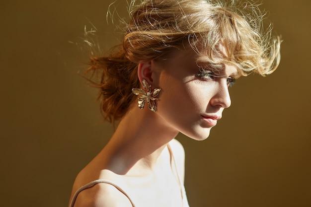 宝石で飾られたイヤリング、女の子の肖像画を持つ完璧な花嫁。美しい髪と清潔で繊細な肌。風に飛んでいる結婚式の髪型のブロンドの女性。手に白い花を持つ少女