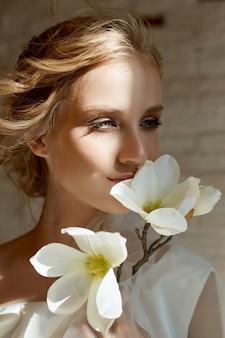 宝石を持った完璧な花嫁、長い白いドレスを着た女の子の肖像画。美しい髪と清潔で繊細な肌。結婚式の髪型金髪女性。手に白い花を持つ少女