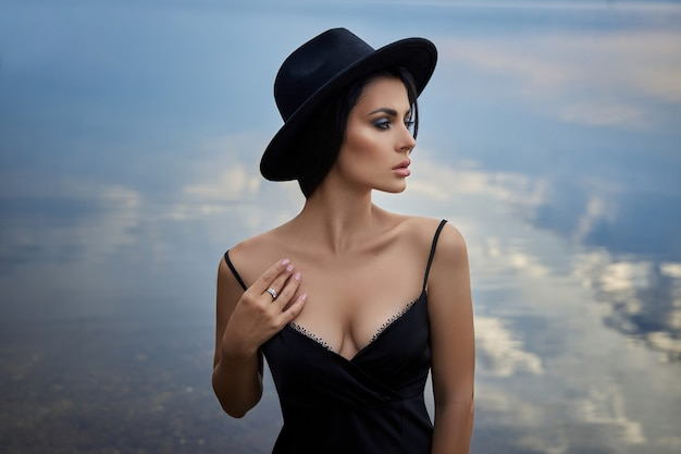 Perfect brunette beauty woman in a black hat and a black dress poses near a lake against a blue sky. long hair woman and beautiful beauty makeup on her face