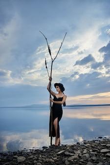 검은 모자와 검은 드레스를 입은 완벽한 브루네트 미녀는 푸른 하늘을 배경으로 호수 근처에서 포즈를 취합니다. 긴 머리 여자와 그녀의 얼굴에 아름다운 아름다움 메이크업