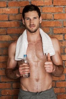 良いトレーニングの後の完璧な選択!肩にタオルで若い筋肉の男の笑顔
