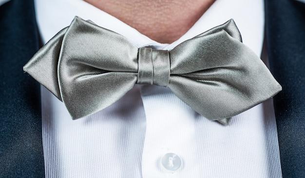 웨딩 파티 앙상블을 위한 완벽한 선택입니다. 흰색 셔츠에 은색 나비 넥타이. 나비 넥타이 컬렉션. 패션 액세서리입니다. 포멀한 스타일. 축제 행사입니다. 휴일 축하.