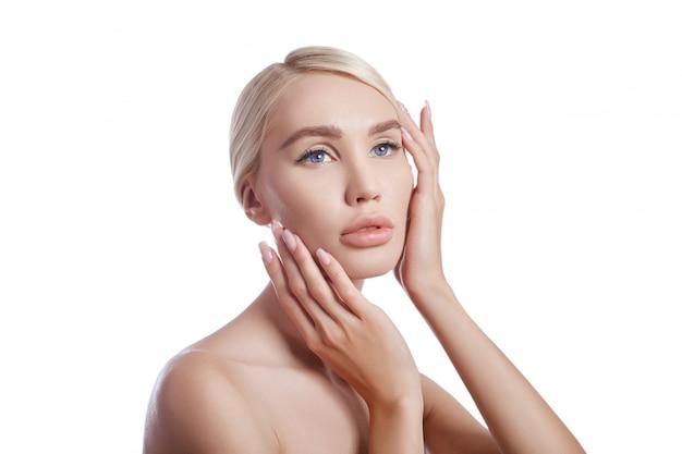 女性の完璧なきれいな肌、しわの化粧品。スキンケアの若返り効果。きれいな毛穴にしわがありません。白い壁にブロンドの女の子を分離します。健康な顔の肌