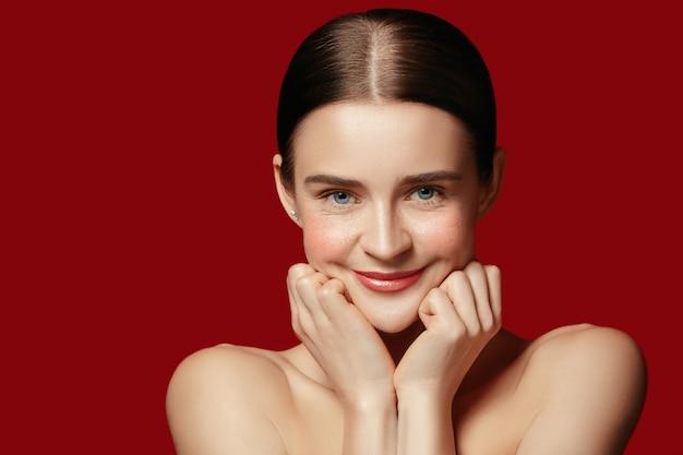 Pelle perfetta e pulita della giovane donna sulla parete rossa dello studio