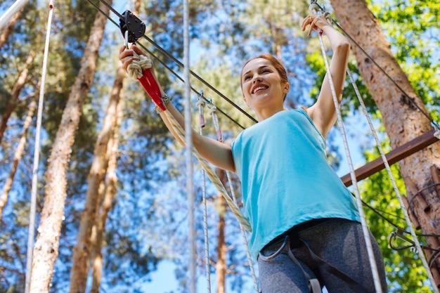 완벽한 하루. 로프 파크 트레일을 따라 움직이기 시작하고 모험 공원에서 쉬면서 자신을 즐기는 즐거운 젊은 여성