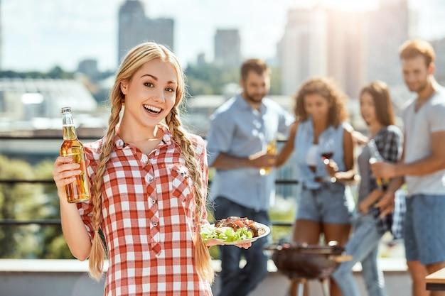 完璧な日若くて陽気なブロンドの女性は食べ物とプレートを持っています