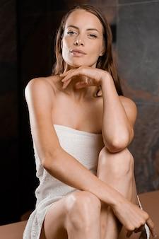 스파에서 모델의 완벽한 얼굴. 수건에 젊은 여자의 뷰티 초상화입니다. 피부 및 바디 케어.