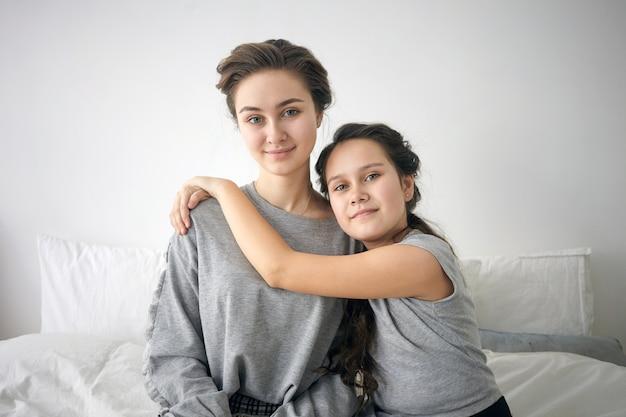 完璧な家族。ベッドに座っている長い黒髪のかわいい12歳の少女の肖像画