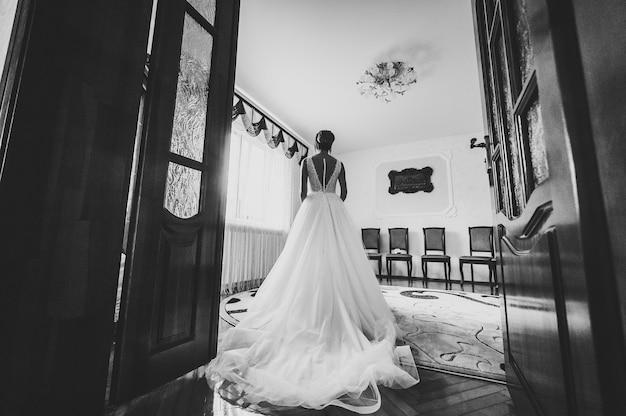 Женщина совершенной фотомодели с прической дома. красивый стиль невесты. свадебная девушка стоит в роскошном свадебном платье возле окна. черно-белое фото.