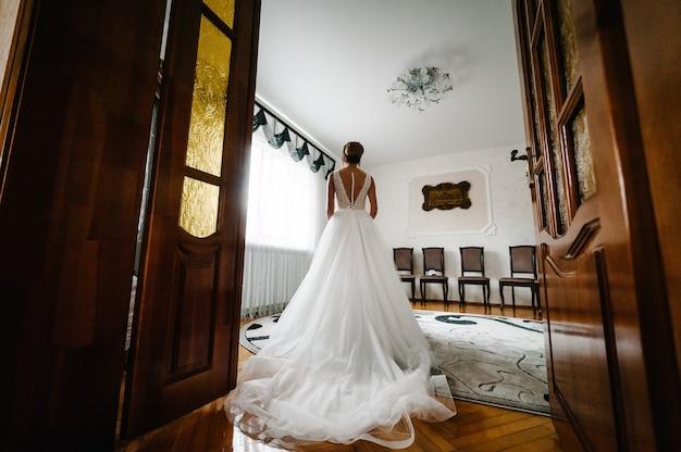 Женщина совершенной фотомодели с прической дома. красивый стиль невесты. свадебная девушка стоит в роскошном свадебном платье возле окна.