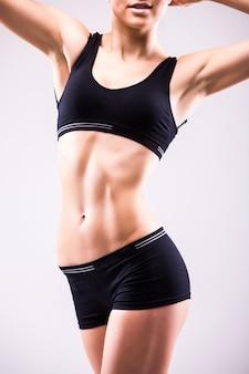 白い壁に分離された完璧なフィットの女性の体