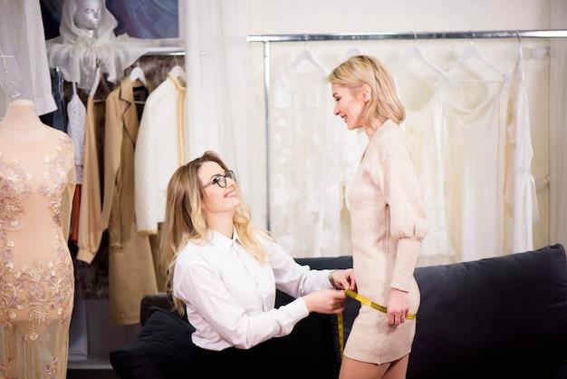 ぴったり。女性のファッションデザイナーとクライアントがアトリエのテーラード服の袖の長さを測定