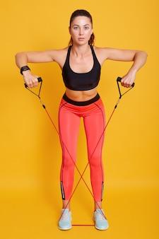 女性の完璧なフィットネス体。フィットネスインストラクターがスタイリッシュなスポーツウェアを着る。エキスパンダーで演習を行う筋肉に合う女性モデル。健康的なライフスタイルとスポーツコンセプト。
