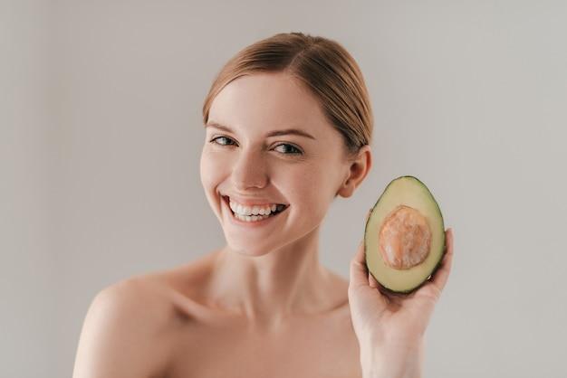 Идеально подходит для ее кожи. красивая молодая женщина с веснушками на лице держит авокадо и смотрит в камеру, стоя на сером фоне