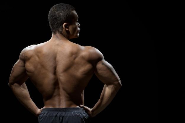 完璧な形。筋肉質の背中でポーズをとっている見事なしっかりした男のスタジオショット