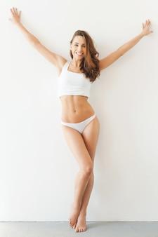 完璧な形。白いタンクトップと白い背景に立ってポーズをとってパンティーの魅力的な若い女性の完全な長さ