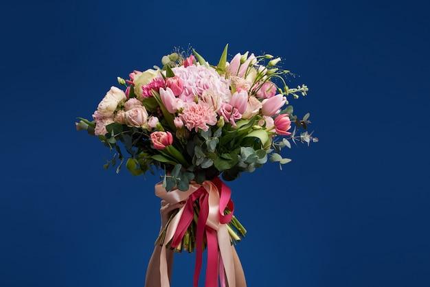 贈り物に最適です。女性の日の素晴らしい花。顔の前で春の花の花束を保持している優しい笑顔の黒髪の女性