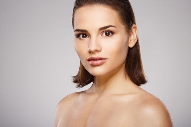 茶色の髪、きれいな新鮮な肌、灰色のスタジオの背景でポーズをとっている裸の肩を持つ完璧な女の子、明るいヌードメイクのモデル、クローズアップ。
