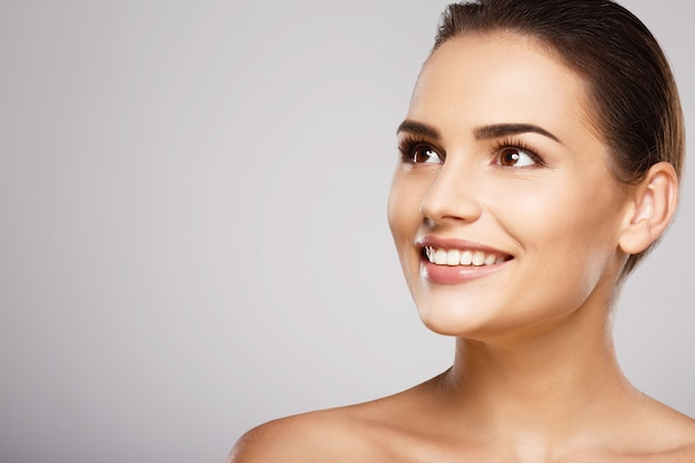 Идеальная девушка с каштановыми волосами, чистой свежей кожей и обнаженными плечами позирует на сером студийном фоне, модель с легким обнаженным макияжем, идеальными зубами, сияющей улыбкой.
