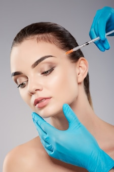 Perfect girl  with nude make up at studio background, doctor's hands wearing blue gloves near patient's face, holding syringe with botex near face, beauty concept, looking down.