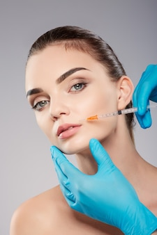 Perfect girl with thick eyebrows at studio background, doctor's hands wearing blue gloves near patient's face, holding syringe near face, looking at camera.