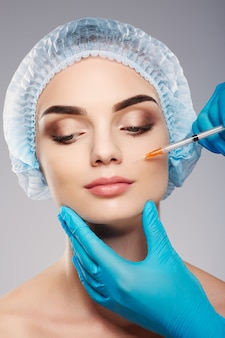 Perfect girl with thick eyebrows wearing blue medical hat at studio background, doctor's hands wearing blue gloves near patient's face, holding syringe near face, looking down.