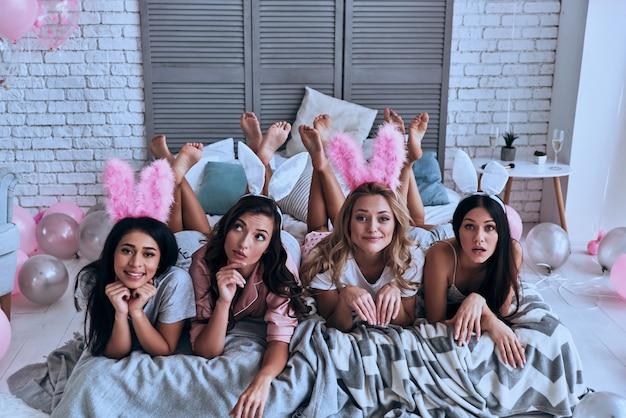 完璧な女の子。バニーの耳に顔を作り、ベッドに横たわっている間笑顔で4人の遊び心のある若い女性の上面図