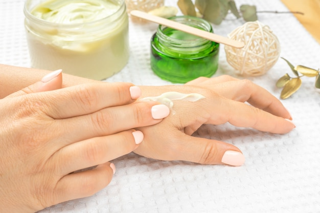 Perfect, groomed adult mature woman's hands using moisturizing, natural herbal cream on pastel pink background. care about clean, soft and smooth hand