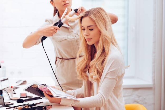 촬영에 완벽한 헤어. 미용사가 화장실에서 컬링 지팡이로 머리를 컬링하는 동안 잡지를 읽는 아름다운 젊은 여성