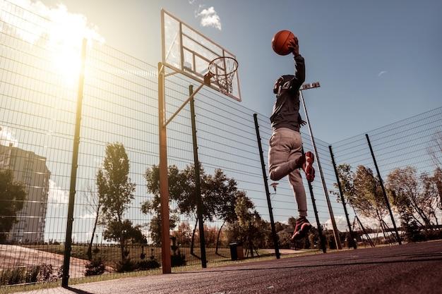 완벽한 히트. 바구니에 던지는 동안 공을 들고 잘 생긴 아프리카 계 미국인 남자