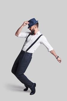 Идеален во всех отношениях. полный рост красивый молодой человек в подтяжках поправляет шляпу и корчит лицо, танцуя на сером фоне