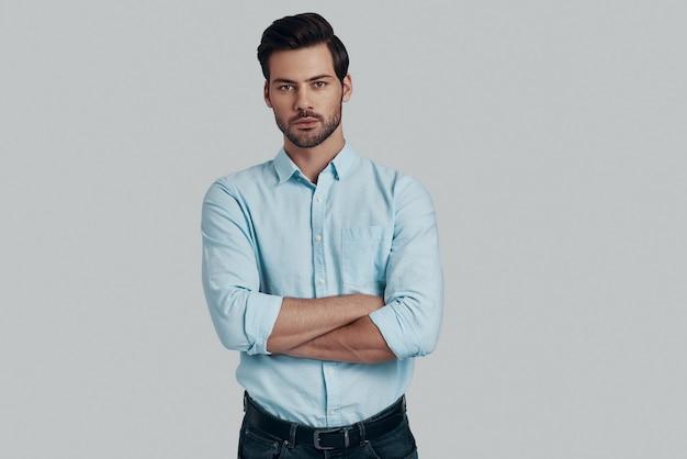あらゆる点で完璧です。カメラを見て、灰色の背景に立っている間腕を組んでいるハンサムな若い男